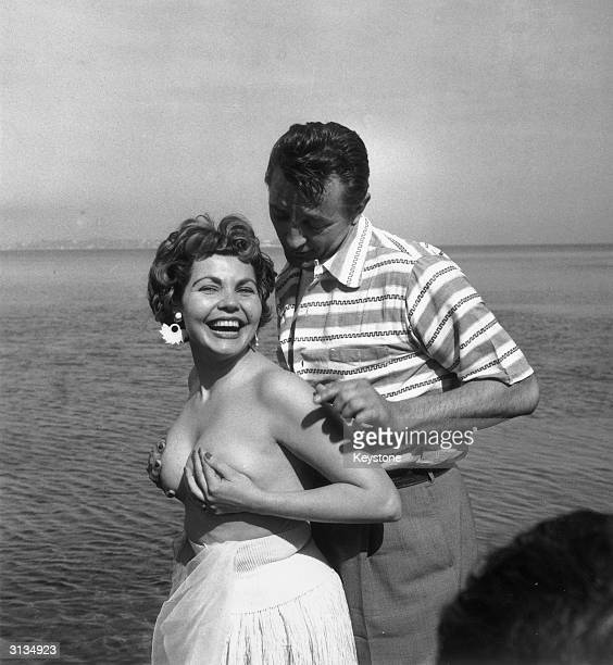 British actress Simone Silva posing topless with the American star Robert Mitchum during the Cannes film festival Having been elected 'Miss Festival'...