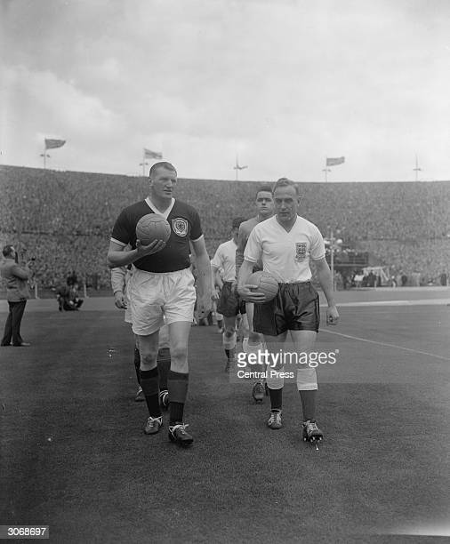 Scotland and Rangers footballer George Young and England and Wolves Captain Billy Wright leading out their respective national teams at Wembley...
