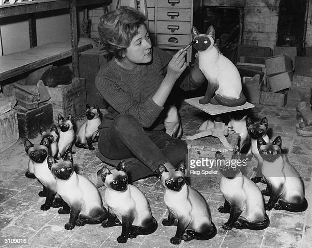 Jennifer Winstanley of Wimbledon painting the faces on Siamese cats at Kensington potteries