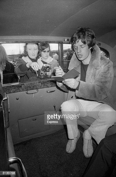 Mick Jagger, the lead singer of the Rolling Stones, signing autographs for fans at London Airport.