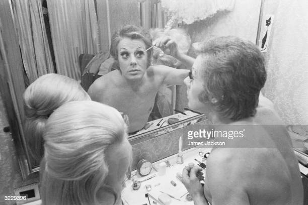 Irish born cabaret drag artiste Danny La Rue applying makeup in his dressing room prior to going on stage