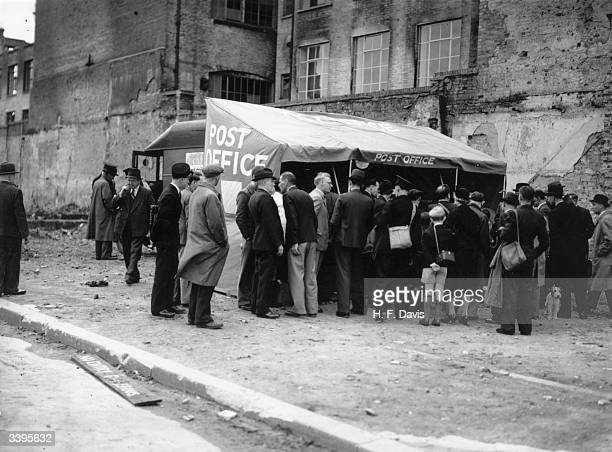 Crowds queue to post letters and telegrams from an experiemental mobile Post Office in London in a scheme to provide postal facilities almost...