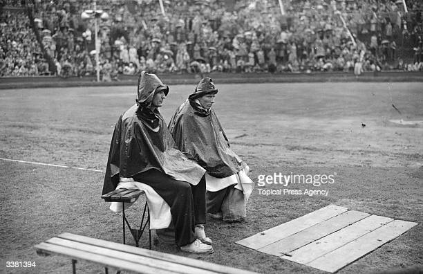 Two Decathlon competitors wait their turn in the rain for the pole vault at Wembley Stadium London