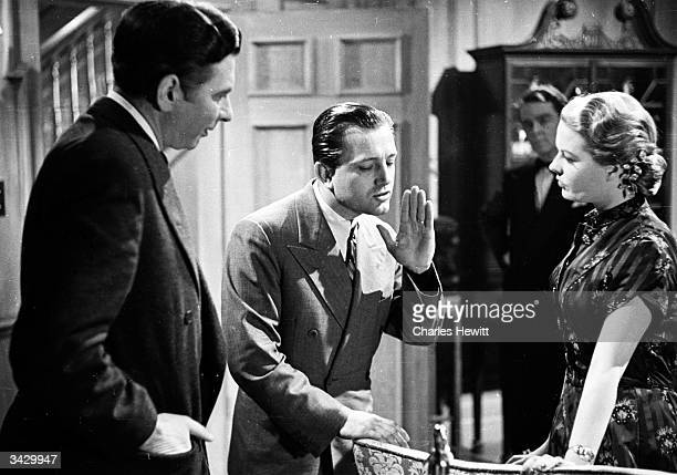Hollywood director Edward Dmytryk instructs actors Robert Newton and Sally Gray in a scene from his latest film 'Obsession', or 'The Hidden Room'. He...