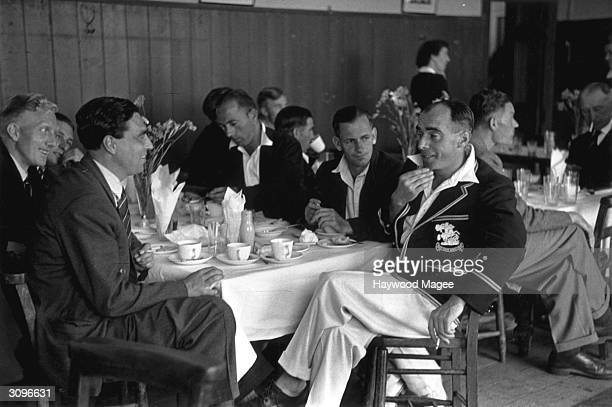Radio broadcaster John Arlott taking tea with some of the players after commentating on the cricket match between Gloucestershire and the New Zealand...