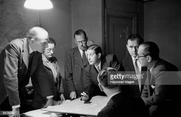 Staff at BBC Radio plan a big outside broadcast Around the table is SJ de Lotbiniere Head of Departmental Staff Ann Robinson secretary Frank Andersen...
