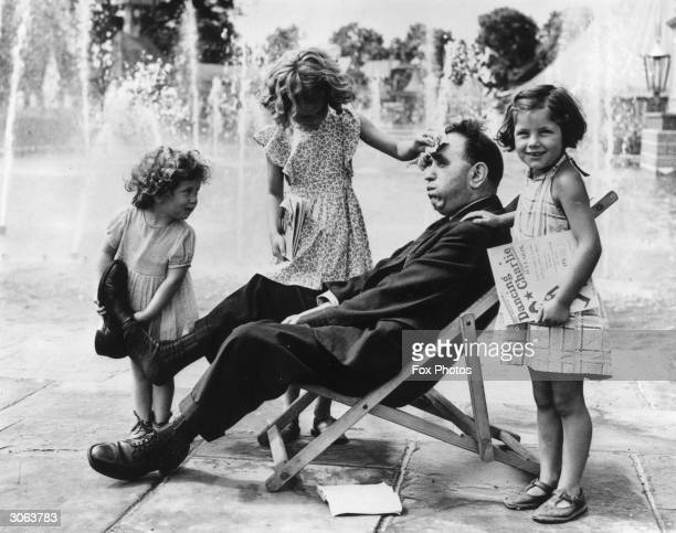 The three little Robson girls Hazel Beryl and Ruth minister to their tired father taking off his shoes mopping sweat from his brow and bringing him...