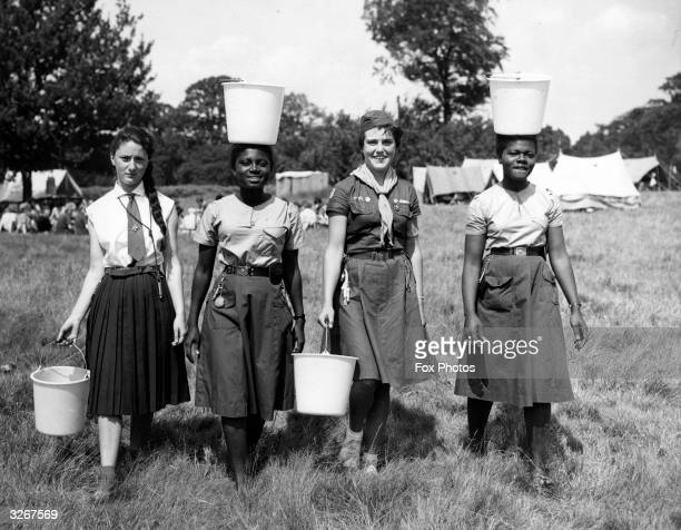 Girl Guides from various countries provide a contrast in watercarrying methods as they go about their daily chores at an international camp at...