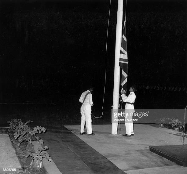 Military officers in ceremonial dress lowering the Union flag at the Jamaican Independence day ceremony