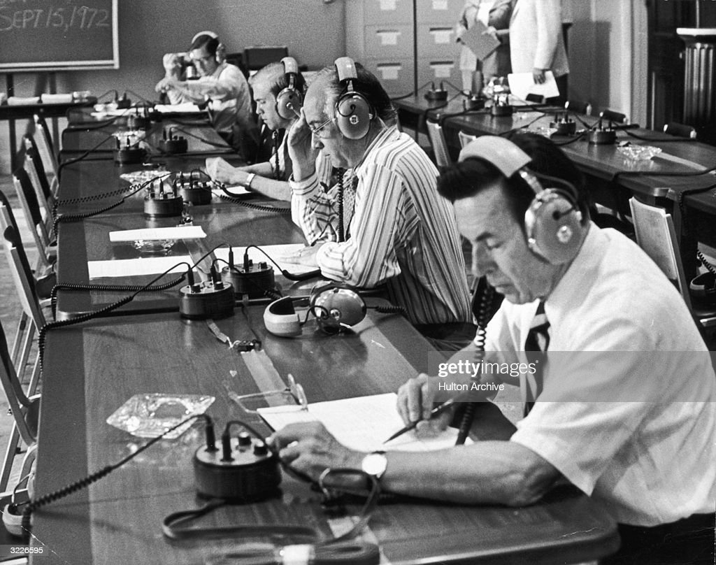 US Representatives Edward Boland of Massachusetts (front), Jack Edwards (second from the front) and others sit at a long table and listen to the White House tapes, Washington, DC. The tapes furnished definitive proof of President Richard Nixon's participation in the Watergate scandal.