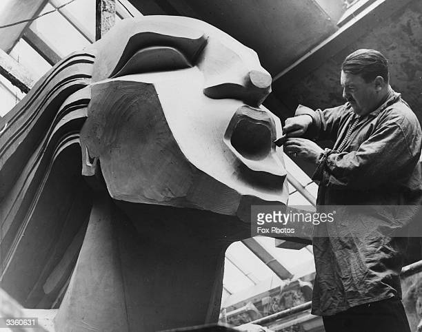 The sculptor Barney Seale at work on the face of one of three enormous figures depicting 'Speed' being constructed for the Chelsea Arts Ball at the...