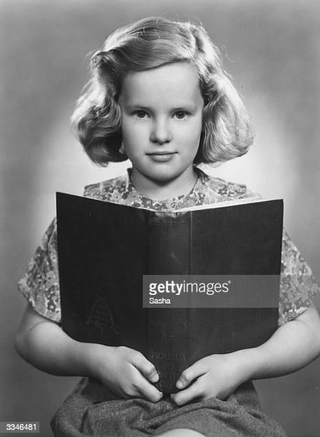 13 year old Irish child actress Peggy Cummins holding a book
