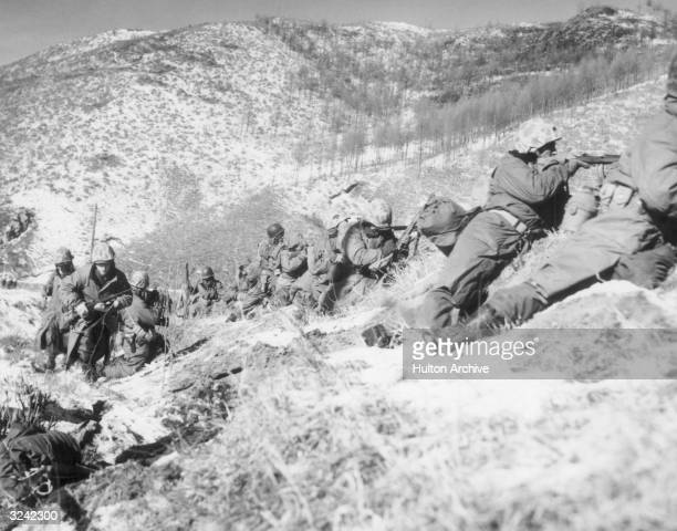 United States Marines infantrymen, taking cover behind large boulders, shoot at North Korean forces during a battle on a snow-covered mountain in the...