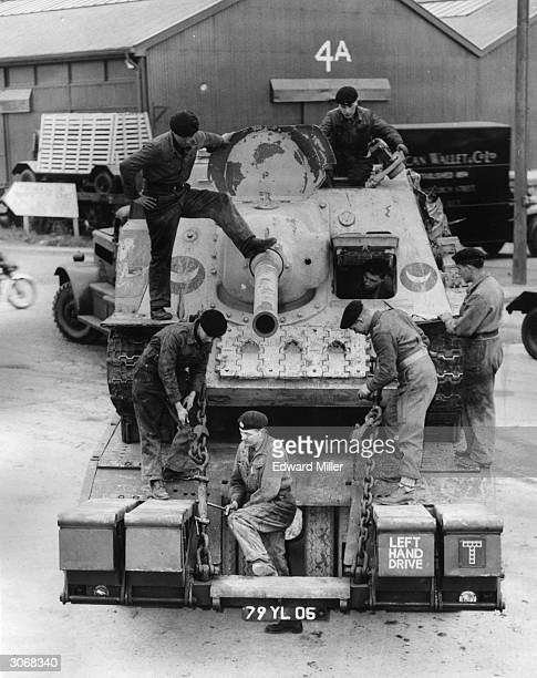 Russian tank captured by British troops in Port Said during the Suez Crisis is loaded onto a tank transporter at Tilbury. Other arrivals were two...