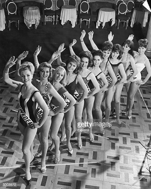 Fulllength group portrait taken from above of Miss Circlorama finalists from around the world waving in swimsuits on the dance floor at the Cafe de...