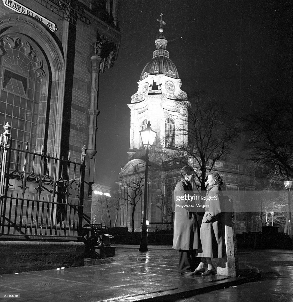 A couple talking by the floodlit cathedral tower in Birmingham. Original Publication: Picture Post - 6979 - The Best And The Worst Of British Cities 4 - Birmingham - pub. 1954
