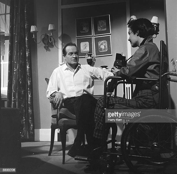 American entertainer Bob Hope posing for wheelchair-bound photographer Delia Dudgeon at Pinewood Studios where he is filming 'Not For Money'.