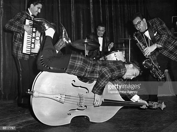 Bill Haley And His Comets rehearsing at the Dominion Theatre London Bass player Al Rex plays his double bass while lying on it