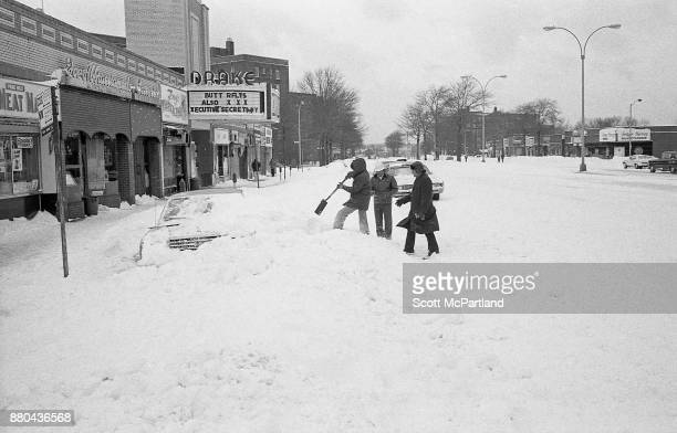 A man digs his car out of deep snow on Woodhaven Boulevard in front of the adult oriented Drake Movie Theater during the Blizzard of 1978