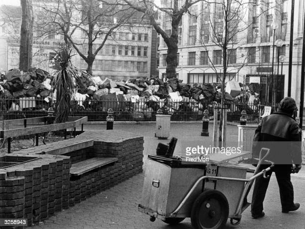 A refuse collector employed by Westminster City Council emptying bins in Leicester Square London which are piled with refuse during disputes over...