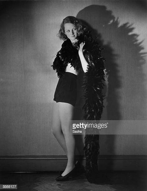 British film actress Elizabeth Allan wearing shorts and a long feather boa