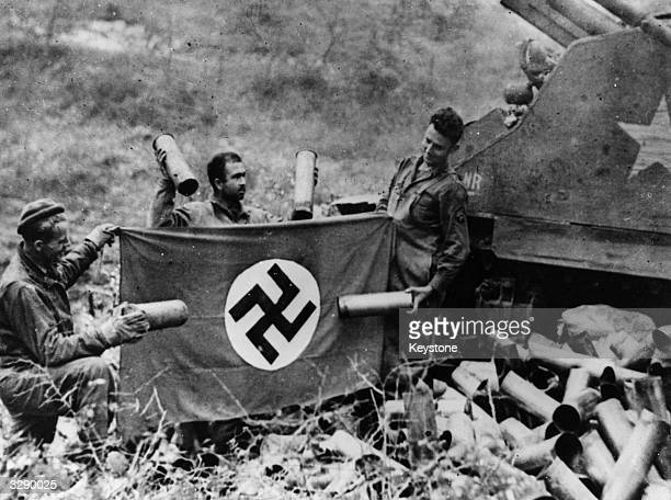 5th Army troops display empty shells and a Swastika flag captured in fighting in San Vityone, Italy.
