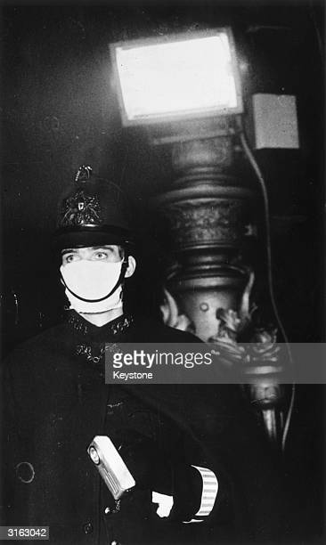 Reg Nicol, a policeman in the City of London, wearing a mask as protection against a severe smog which has virtually blacked out the capital....