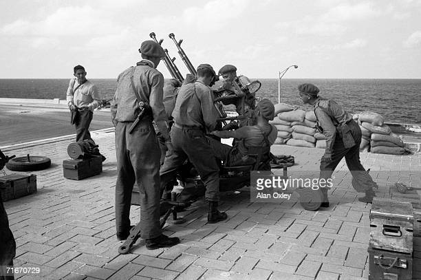 Cuban militiamen set up an antiaircraft gun on a gas station roof in front of the luxury Riviera Hotel on Havana's Malecon Drive as Fidel Castro...