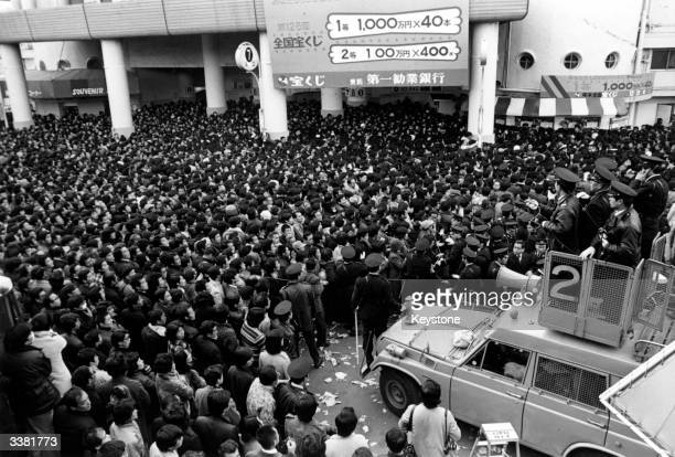 Watched by the police crowds in Tokyo keep their eyes glued to a board on which are to be displayed the winning numbers of the Grand National Lottery...
