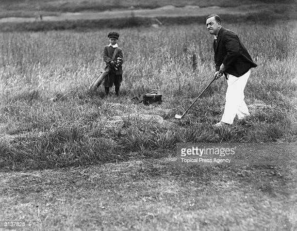 Mr Summehays playing out of the rough during an American golf tournament at Stoke Poges Buckinghamshire watched by a very small caddie