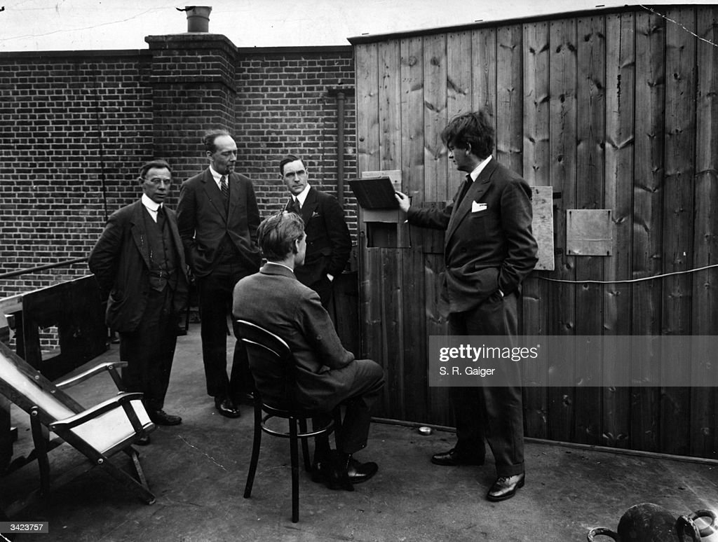 Scottish engineer John Logie Baird (right) demonstrating television transmissions illuminated by natural daylight on the roof of his laboratory at Long Acre.
