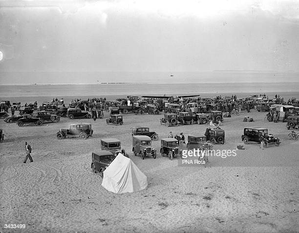 Holidaymakers and their cars crowd the sands at a popular beach resort