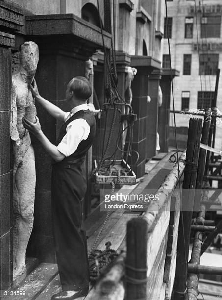 A workman examining one of the Epstein statues on the front of Rhodesia House A decision has been made to remove them