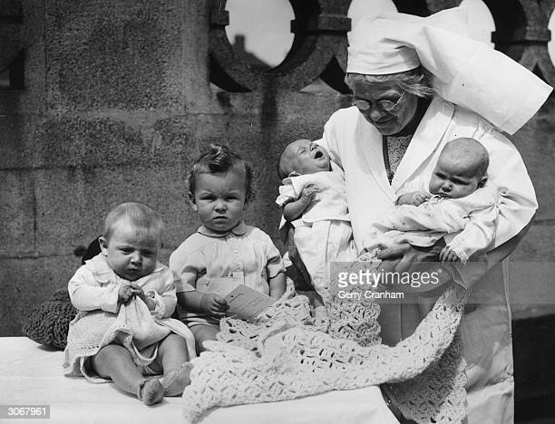 A nurse prepares the young contestants in a baby show at the Claremont Central Mission in Pentonville London First prize for the lucky winner is two...
