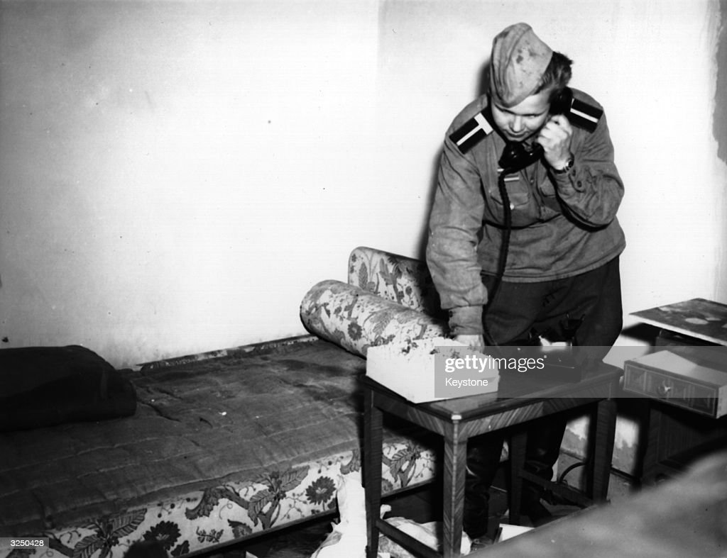 A Russian soldier using Eva Braun's phone in her bedroom in Hitler's shelter, at the Chancellery building, Berlin.