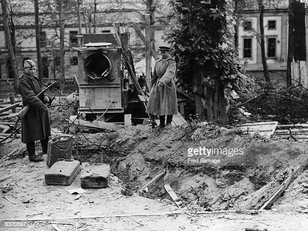 Two Russian soldiers point out what is alleged to be Hitler's grave at the back of the Chancellery in Berlin. Alongside are petrol cans.
