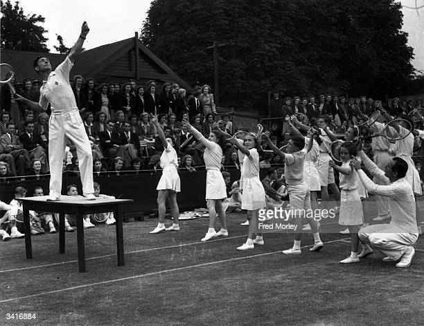 British tennis star Dan Maskell demonstrates the serving technique, whilst fellow player Fred Perry gives a helping hand to young players at Surbiton...