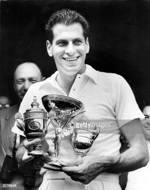 American tennis player Dick Savitt with some of his trophies after beating Ken McGregor of Australia in the men's singles final at the Wimbledon Lawn...