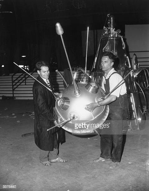 Russian workmen carry a model of one of the Sputnik satellites in front of a model of a rocket nosecone at the Russian Trade Fair at Earl's Court in...