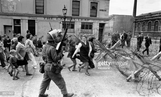 Heavily armed British troops patrolling a civil rights march in the Falls Road area of Belfast The marchers protesting against the imposition of a...
