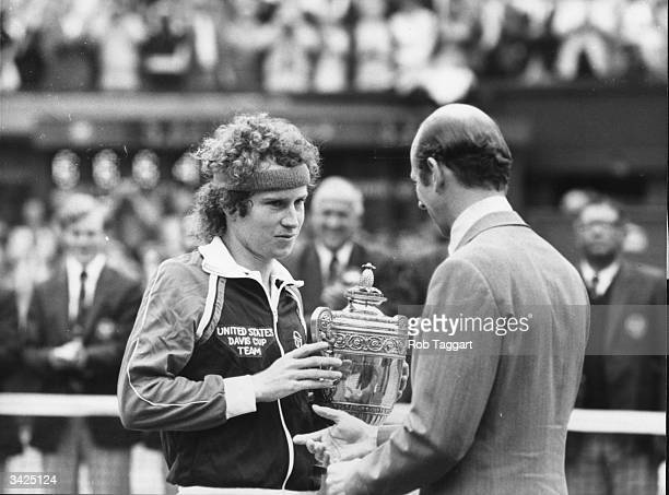 American tennis star John McEnroe receiving his trophy from the Duke of Kent after beating Bjorn Borg in the Men's Singles Final at Wimbledon