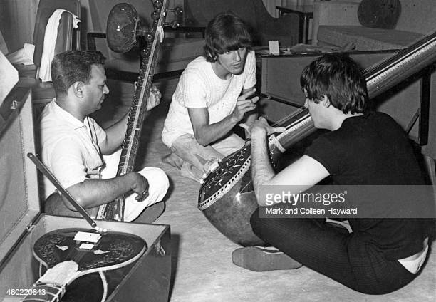 Paul McCartney and George Harrison centre from The Beatles are given a sitar demonstration in Rikhi Ram's instrument shop in New Delhi India on 6th...