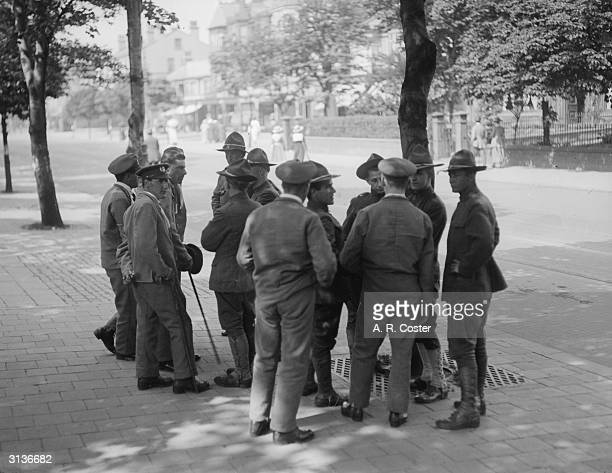 Group of American and British soldiers talking in a street in Southport, Lancashire.