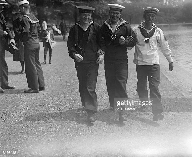 LR American British Japanese sailors walk arminarm in the park