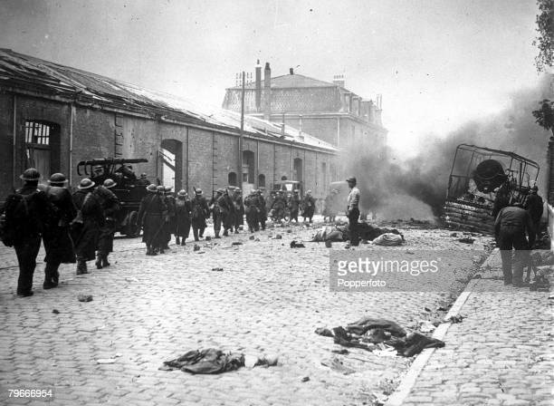 6th June 1940 World War II British soldiers marching thorough a debrislittered street of Dunkirk during the bombardment as the BEF were evacuated