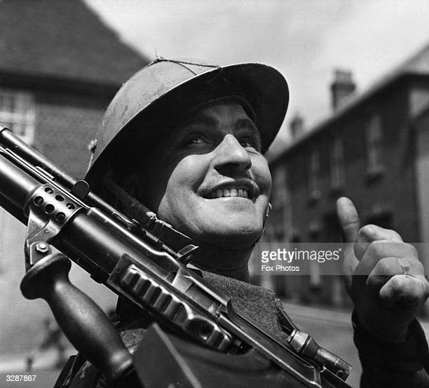 British soldier, encamped in a small English village, gives the thumbs-up as he awaits his orders for D-Day.