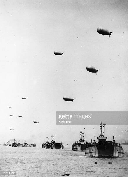 A long line of LST or Landing ShipTanks each towing a protective barrage_balloon are seen heading away from the English coast carrying supplies to...