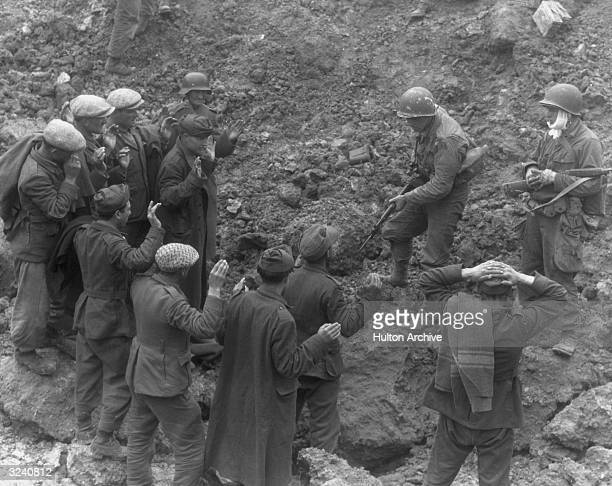 A US soldier holds a group of German troops and laborers at gunpoint in a ditch during World War II Omaha Beach Normandy France An American soldier...