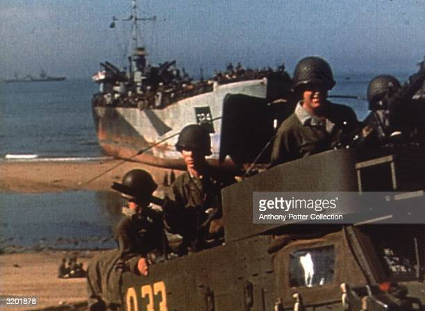 Allied troops ride in an open truck while a landing craft sits on the shore in the background on a beachhead in Normandy, France, World War II, D-Day.