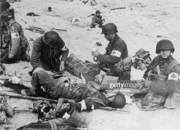 American medics administer first aid to wounded soldiers on Utah beach in Normandy France whilst in the background other troops 'digin' in the soft...